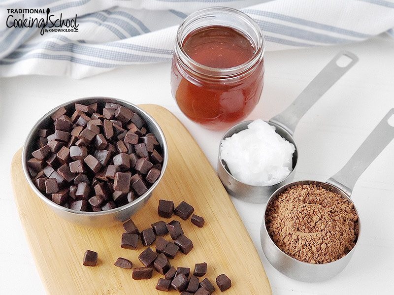 small metal bowl of chocolate chunks on a wooden cutting board next to an array of ingredients necessary to make homemade chocolate, including honey, coconut oil, and cocoa powder