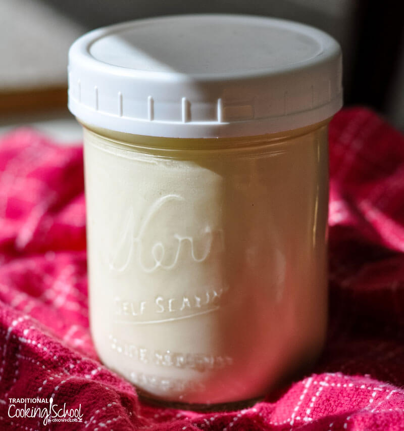 pint-sized glass Mason jar with a plastic lid filled completely with raw cream