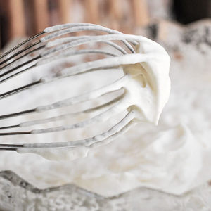 close-up shot of a whisk that has been used to make whipped cream so that it is covered in foamy cream