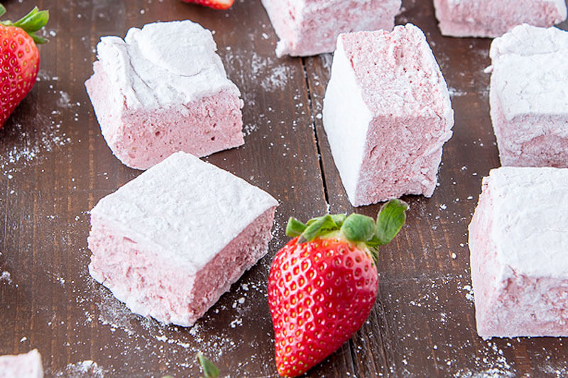 assortment of pale pink strawberry marshmallows, on wooden surface, next to fresh strawberries