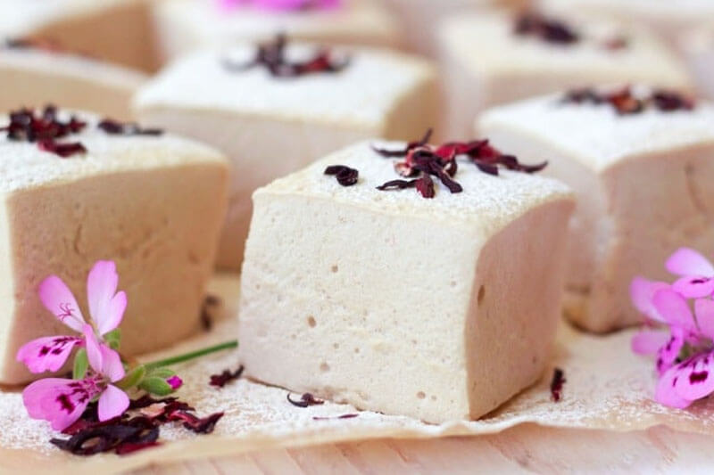 assortment of creamy white marshmallow cubes, garnished with dried hibiscus, arranged next to fresh hibiscus flowers