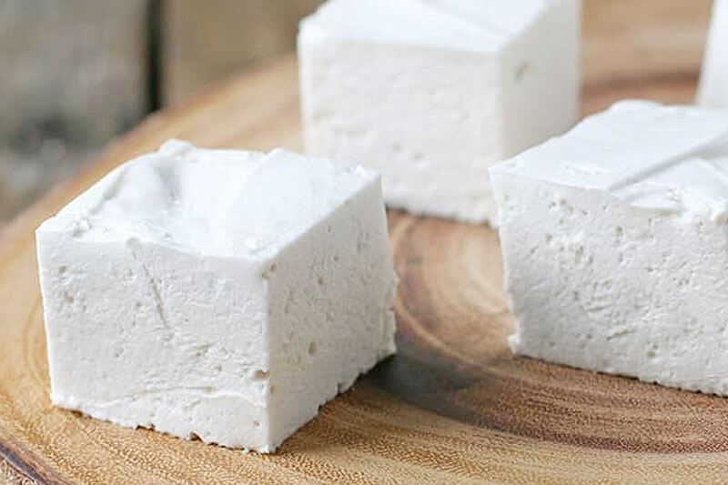 three white marshmallows on a wooden surface