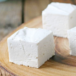 three homemade marshmallow squares, with spongey texture and sharply cut edges