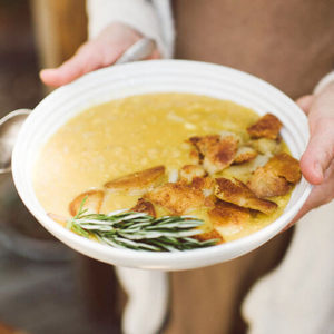 woman's hand holding a large white ceramic bowl of golden-colored, creamy soup topped with chicken and fresh herbs