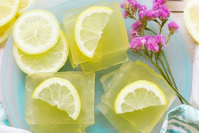 homemade lemon jello arranged on a platter with decorative lemon slices and pink flowers