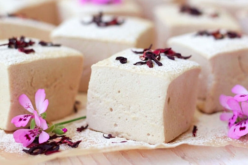 homemade hibiscus marshmallows scattered with fresh and dried hibiscus flowers