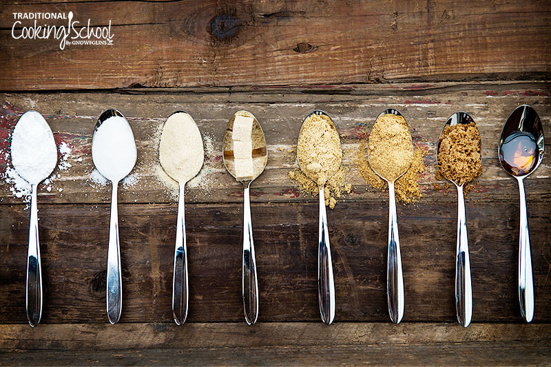 spoons of different types of sugar arranged to show a gradient of most processed (white) to least (brown)