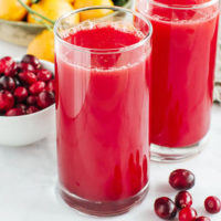 two glasses of homemade cranberry juice with oranges and fresh cranberries in the background