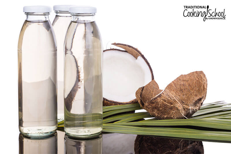 three tall glass jars of MCT oil next to a coconut split open into two halves