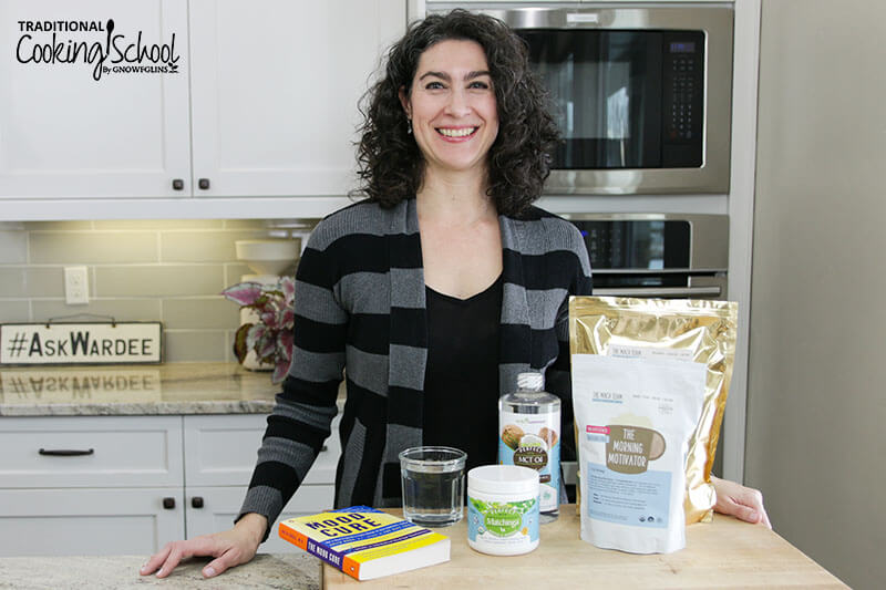 woman smiling in a kitchen with an array of natural energy boosters in front of her, including maca powder