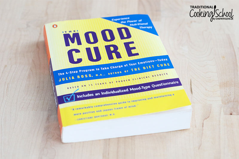 The Mood Cure book by Julia Ross on a wooden surface