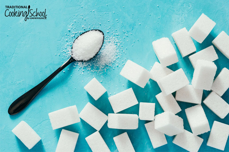 sugar cubes and a spoonful of sugar on a bright blue background