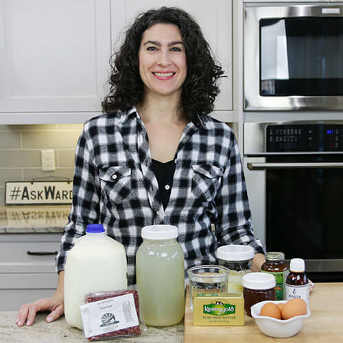 smiling woman standing in a kitchen with an array of healthy, natural cold and flu remedies to boost your immune system, including raw milk, grass-fed butter, cod liver oil, and more,