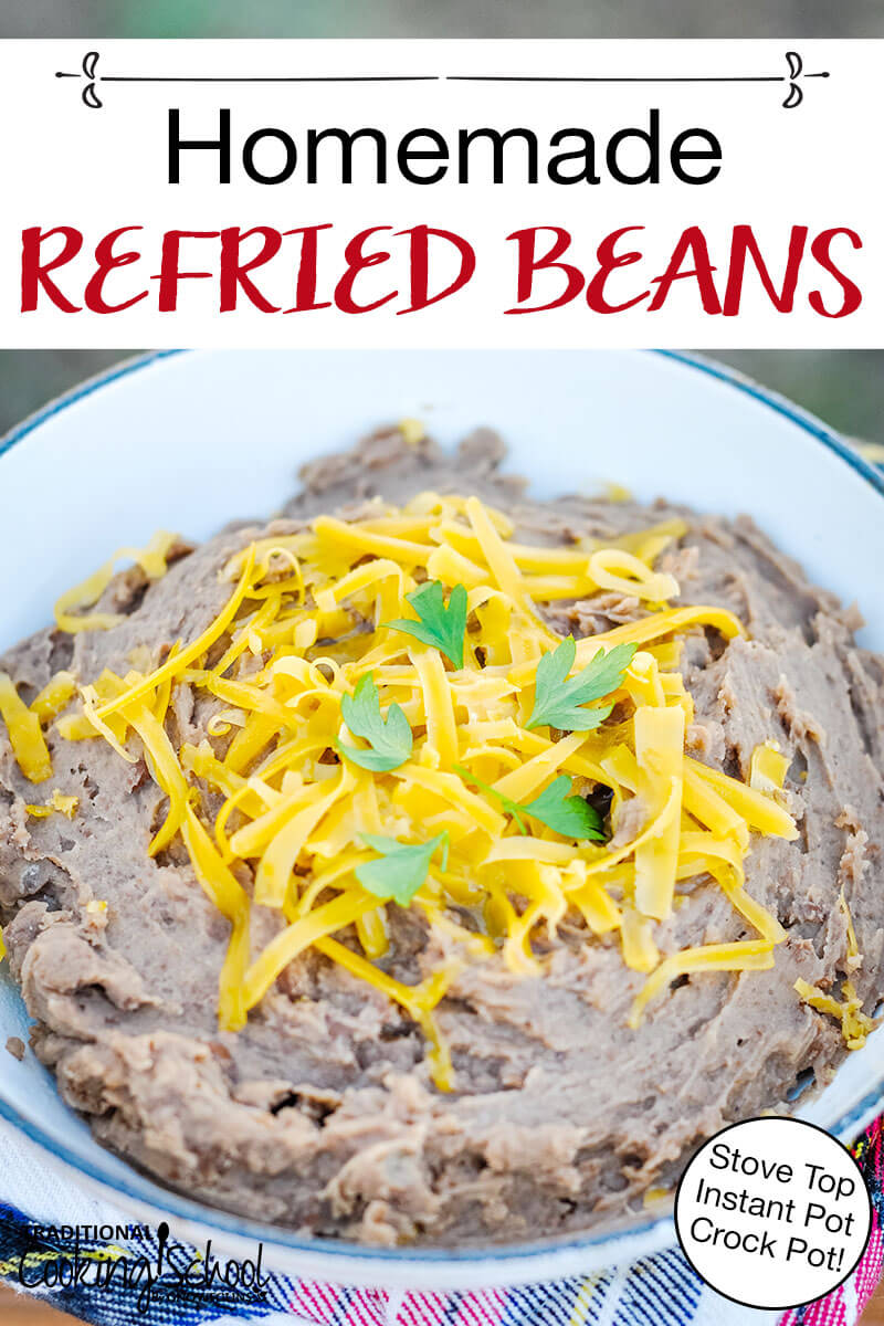 """bowl of refried beans topped with grated cheddar cheese and fresh cilantro, with text overlay: """"Homemade Refried Beans (Stove Top, Instant Pot, Crock Pot!)"""""""