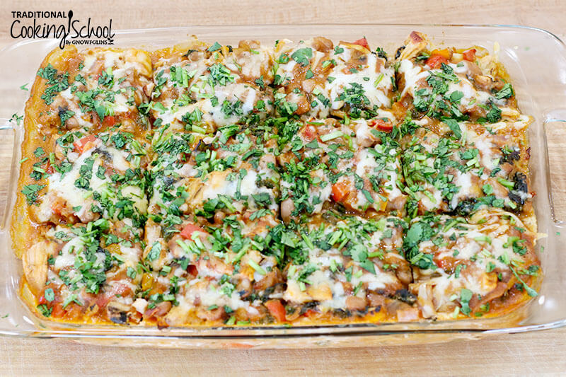 chicken enchilada casserole in a glass casserole dish topped with fresh herbs