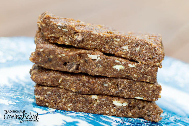 stack of four homemade Larabars made out of soaked and dehydrated nuts on a blue and white ceramic plate