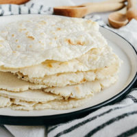 stack of homemade tortillas with golden brown spots on a ceramic plate