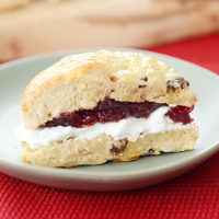 fluffy scone wedge, spread with cream and jam in the middle