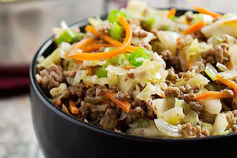 egg roll in a bowl with shredded carrots, cabbage, onions, and ground beef