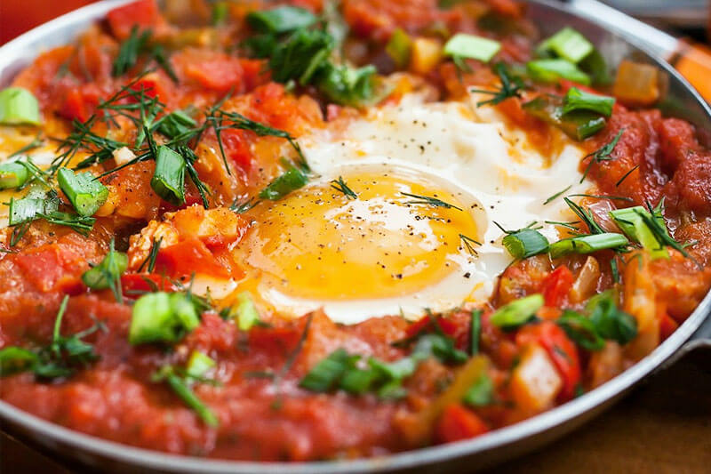 shakshuka with egg, tomato, and chopped fresh herbs