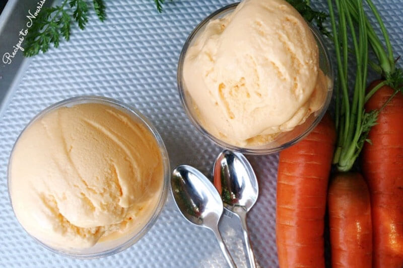 carrot cinnamon frozen yogurt in two glass bowls next to spoons and fresh carrots