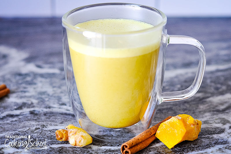 foamy, golden-colored turmeric latte in a clear glass mug