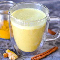golden foamy drink in a clear glass mug