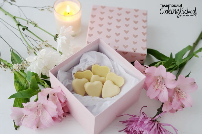 decorative pink box of cream-colored, heart-shaped candies, surrounded by pink flowers and a candle