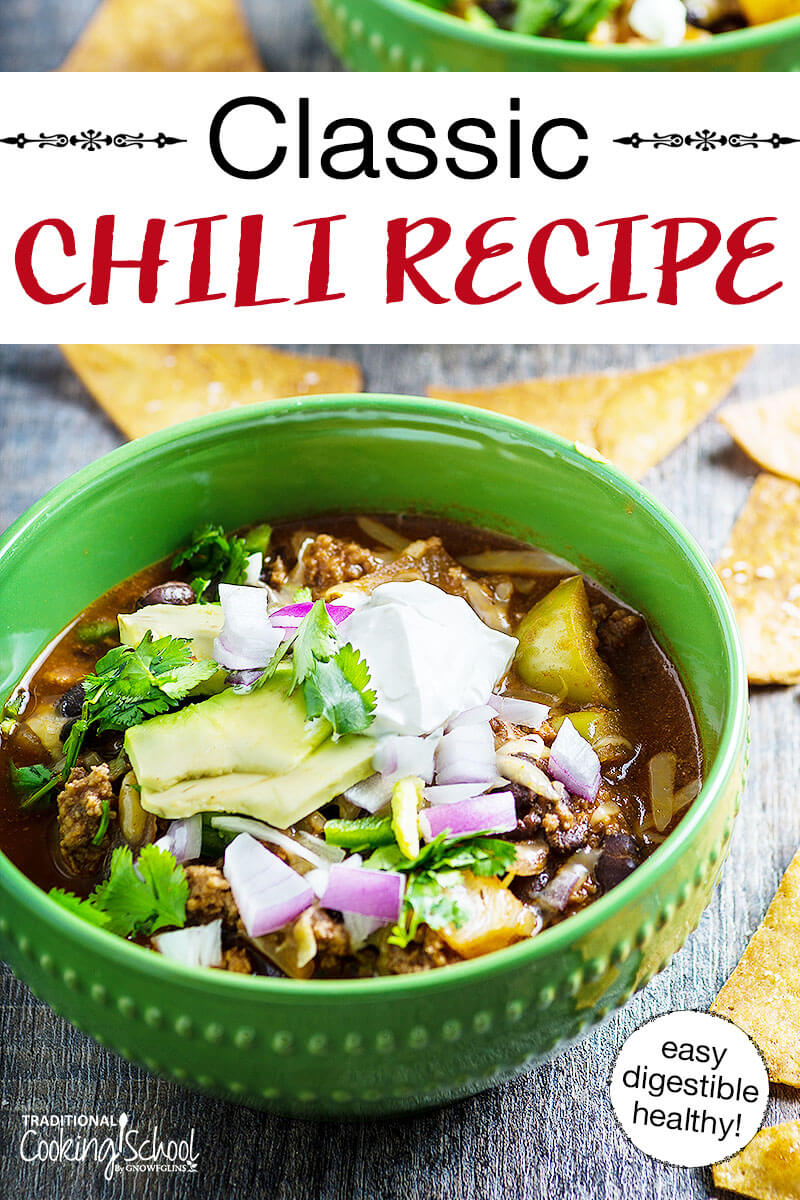 "Green bowl filled with chili that's topped with diced red onion, avocado slices and sour cream. Tortilla chips are spread on the table. Text overlay says, ""Classic Chili Recipe"""