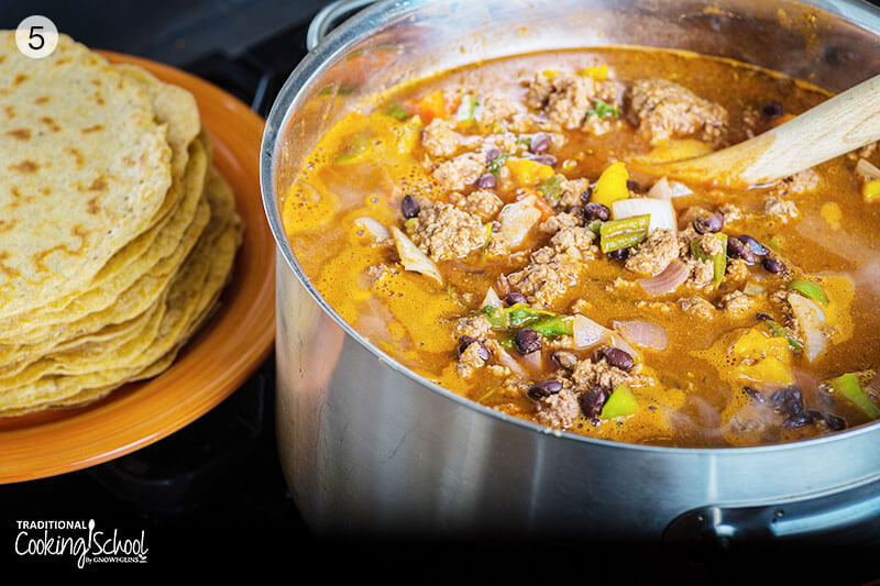 stock pot of beans, ground beef, and veggies simmering next to a stack of tortillas on a plate