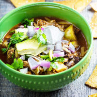 green bowl of chili, garnished with sour cream, avocado, herbs, and purple onion