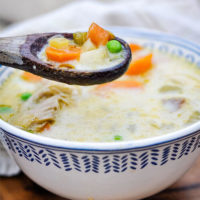 wooden spoon scooping into a colorful veggie soup of chicken, carrots, and peas