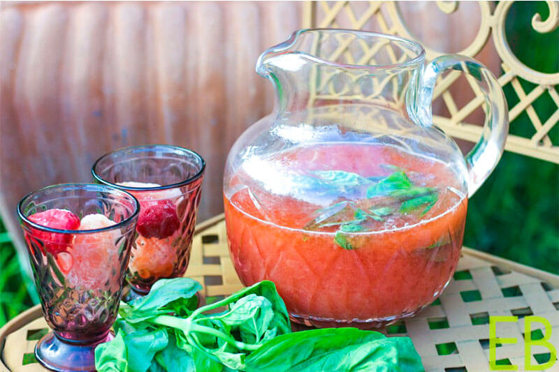 strawberry basil switchel in a pitcher with two glasses nearby for serving