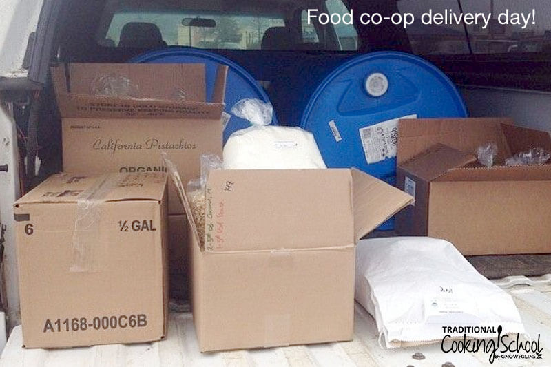 boxes, bags, and tubs of bulk food in the bag of a truck with the tailgate down
