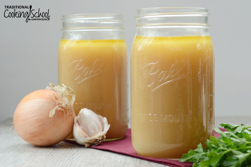 two quart-sized glass jars of broth with assorted veggies nearby