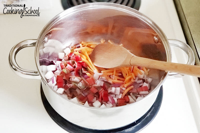 stainless steel pot on a stove with veggies for soup sauteing inside