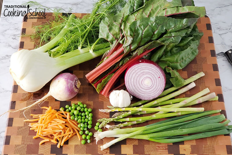 array of veggies on a wooden cutting board, including asparagus, green onion, fennel, chard, onion, garlic, turnip, peas, and grated carrots