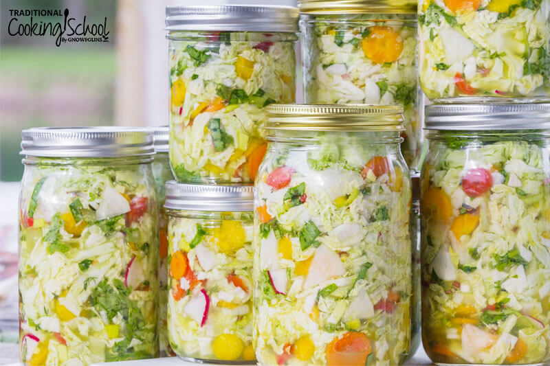 stack of mason jars full of fermented cabbage and other veggies