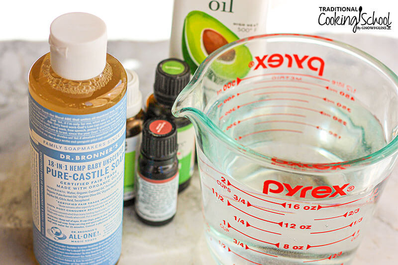 array of ingredients to make homemade hand soap: liquid castile soap, antibacterial essential oils, avocado oil, and water in a Pyrex measuring cup