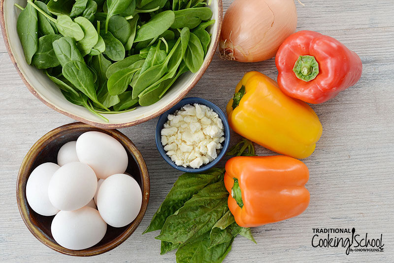 array of ingredients, including spinach and fresh herbs, feta cheese, eggs, bell peppers, and an onion