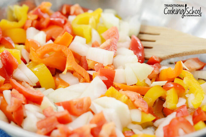 sauteing a medley of veggies, including bell pepper and onion