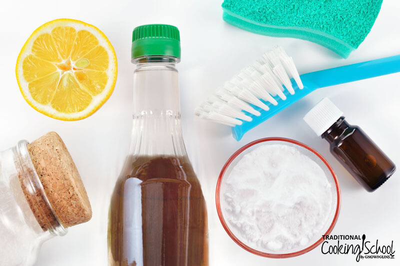 array of natural cleaning ingredients, includnig half a lemon, baking soda, and apple cider vinegar
