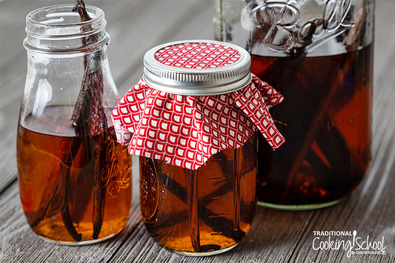 assorted jars of vanilla beans and vodka, infusing to make vanilla extract