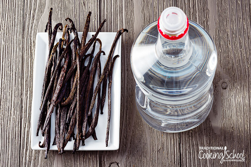 bottle of vodka next to a small plate of vanilla beans
