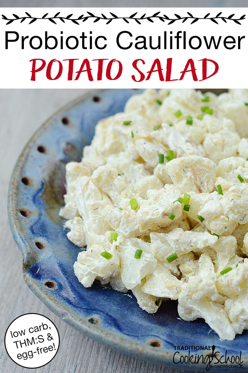 """fauxtato salad sprinkled with chives in a blue ceramic dish, with text overlay: """"Probiotic Cauliflower Potato Salad (low carb, THM:S & egg-free!)"""""""