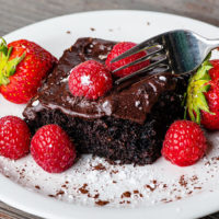 A white plate with a piece of chocolate frosted chocolate cake topped with fresh raspberries and strawberries