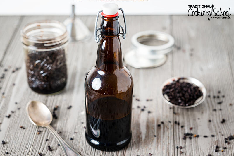 Elderberry tincture in an amber glass bottle with a spoon next to it and dried elderberries on the table.