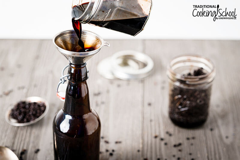 Elderberry tincture being poured into an amber glass bottle.