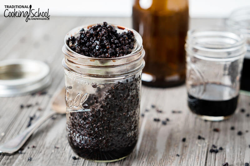 Elderberries in a fine mesh strainer with elderberry tincture in a jar.