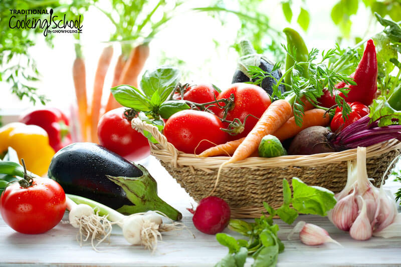 array of fresh vegetables in a basket and on a wooden surface